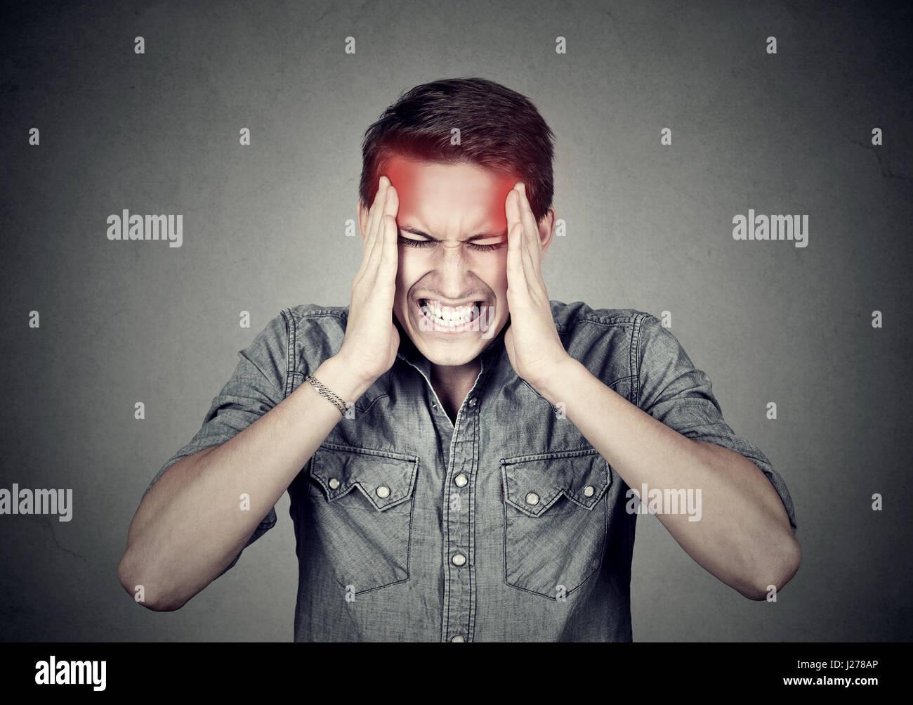 Subrayó el hombre con dolor de cabeza aislado sobre fondo de pared gris Foto de stock