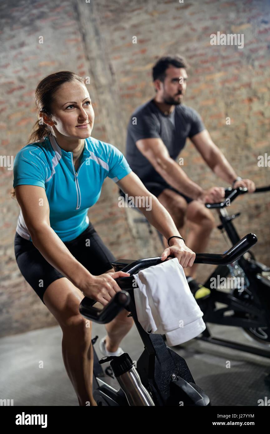 Colocar deportivo pareja en ropa deportiva haciendo la formación en bicicleta Imagen De Stock