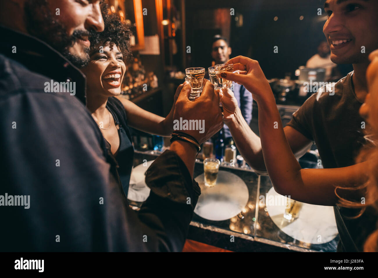 Amigos tostado mutuamente con disparos de vodka mientras disfruta de una relajante noche juntos en el pub. Grupo Imagen De Stock
