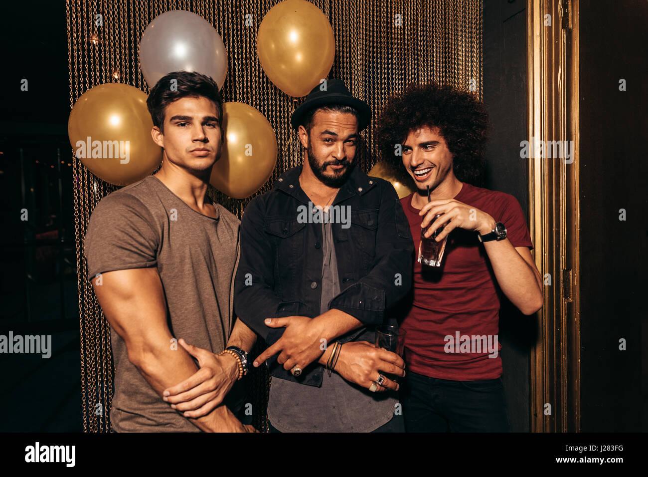 Retrato de tres jóvenes la fiesta en la discoteca. Grupo de hombres que tienen buenos tiempos en el pub. Imagen De Stock