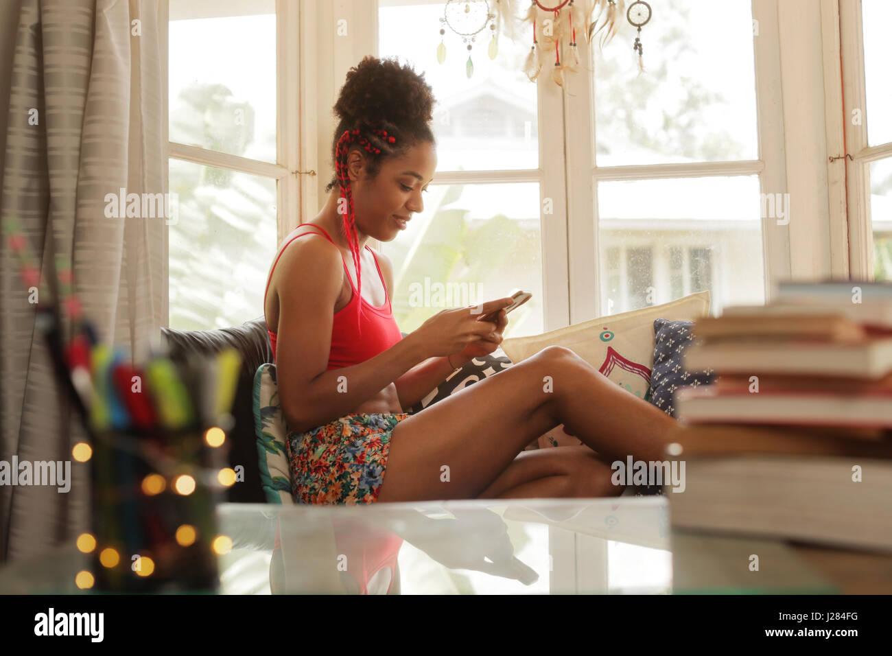Chica negra tumbado en el sofá y utilizando el smartphone, joven afroamericana relajantes con teléfono Imagen De Stock