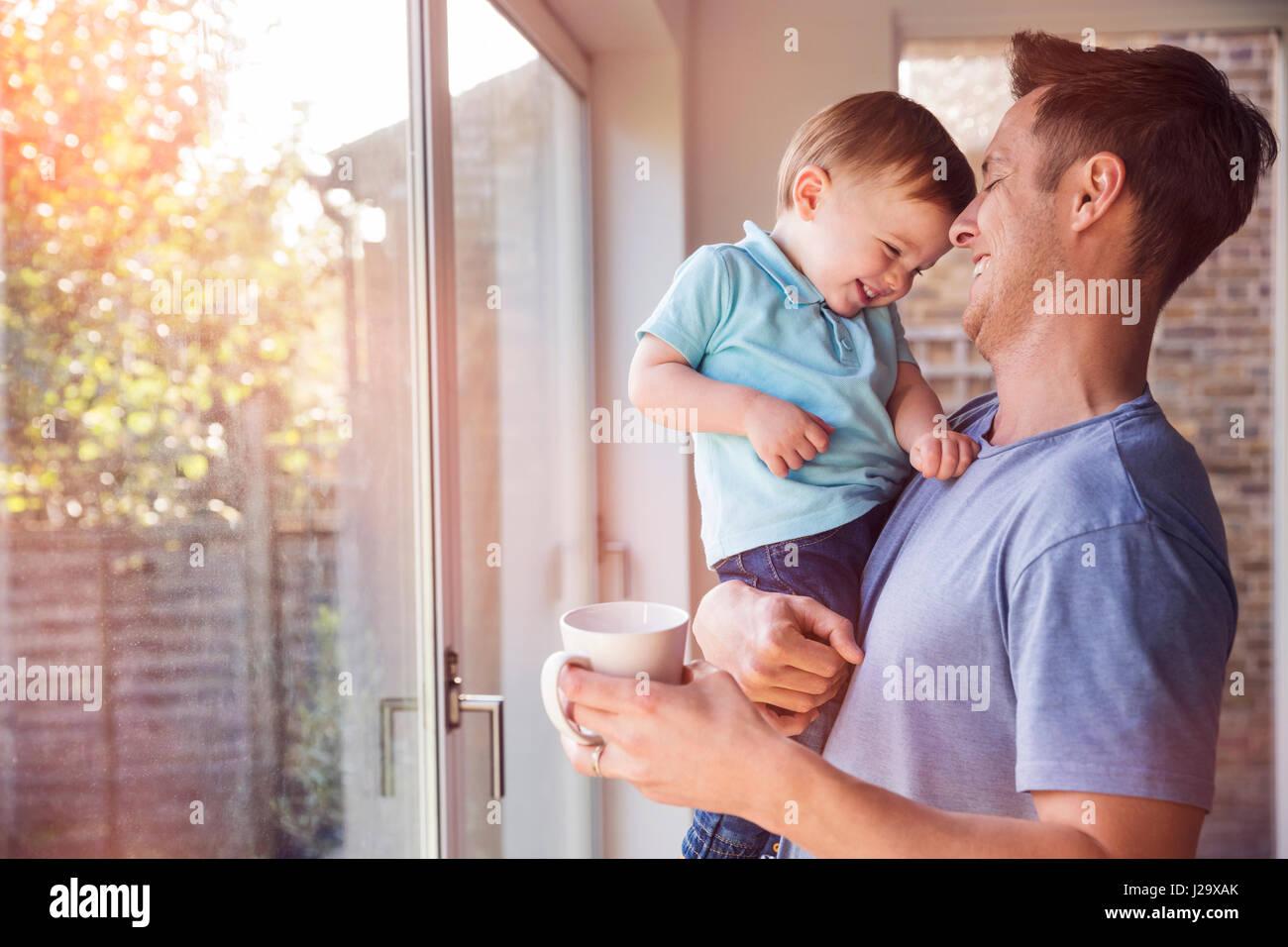 El padre tiene un hijo pequeño mientras bebe café en casa, por la ventana Imagen De Stock