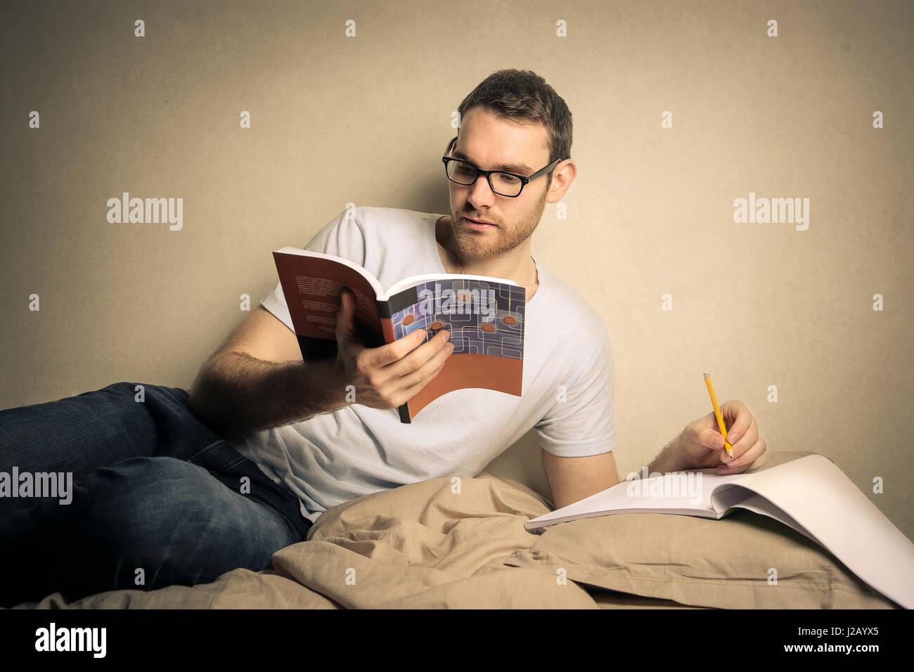 El hombre estudiando desde libros y tomando notas Imagen De Stock
