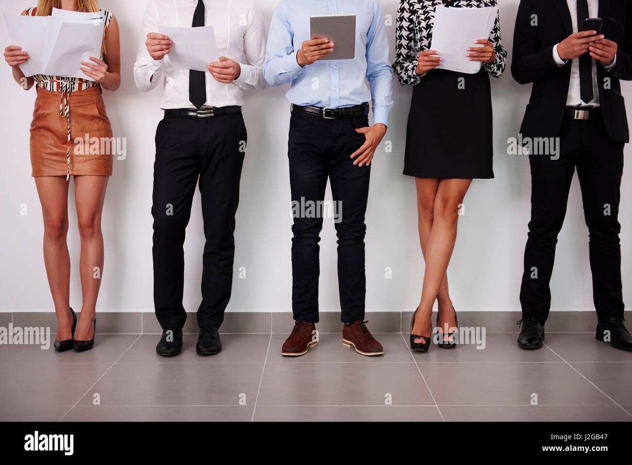 Las piernas de los seres humanos de gente que espera para una entrevista de trabajo Imagen De Stock