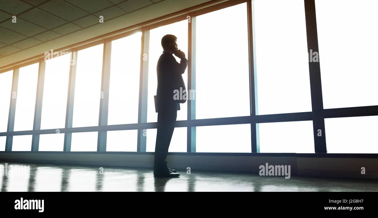Disparo de longitud completa del hombre de negocios de pie cerca de la ventana de la oficina y hablando por teléfono Imagen De Stock