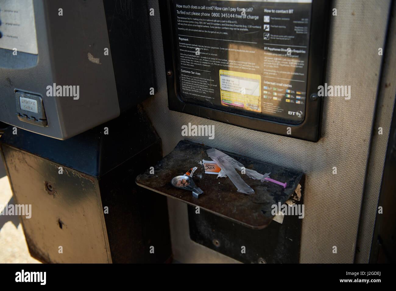 Los escombros dejados por un usuario de drogas en un cuadro teléfono en Cardiff Foto de stock