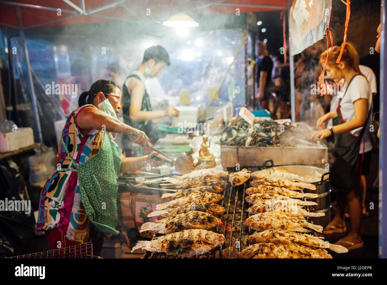 CHIANG MAI, Tailandia - 27 de agosto: vendedor de comida cocineros pescados y mariscos en el mercado del sábado Imagen De Stock