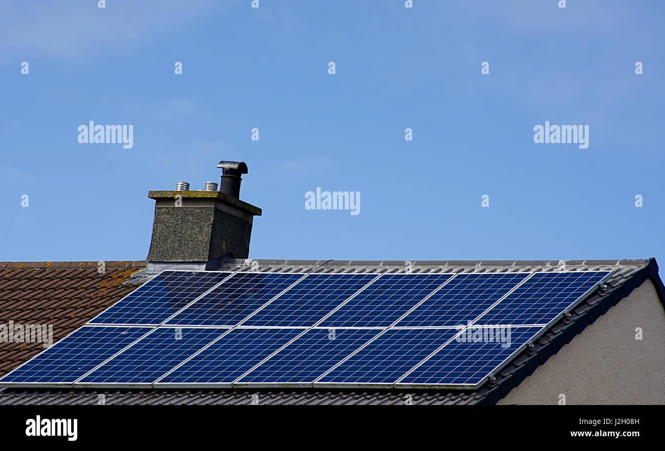 Paneles solares en el techo de la casa inclinada con el cielo azul de fondo, el norte de Gales, Reino Unido Reino Imagen De Stock