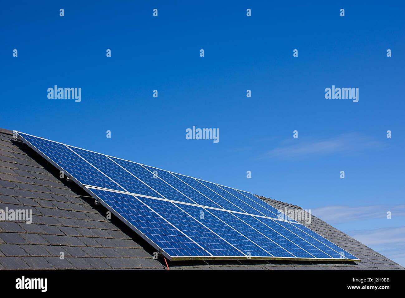 Paneles solares en el techo de la casa con el cielo azul de fondo, el norte de Gales, Reino Unido.La energía Imagen De Stock