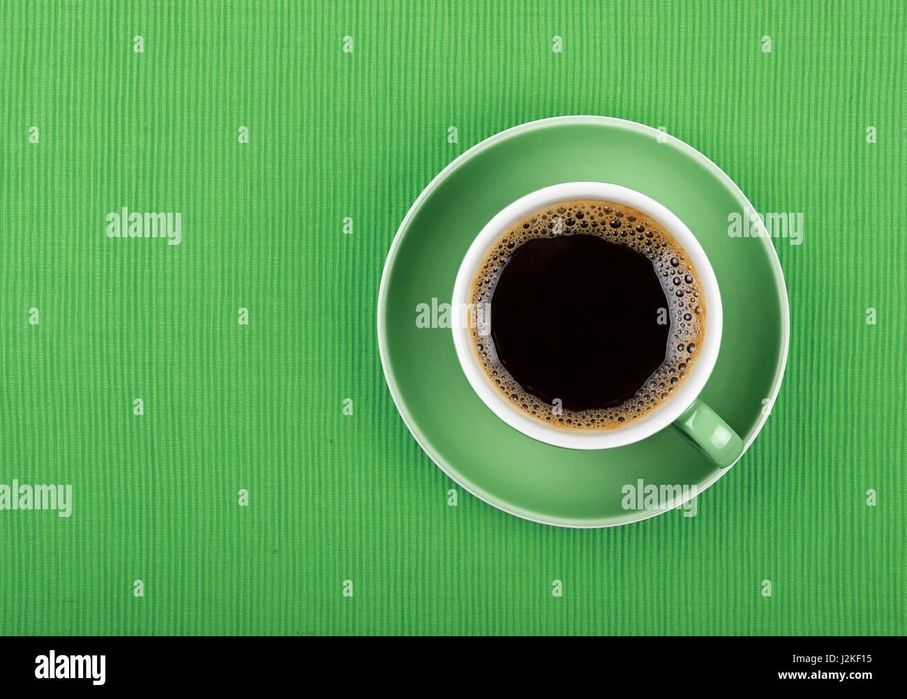 Taza llena de negro americano o café instantáneo en un platito sobre un mantel verde, cerrar, niveles Imagen De Stock