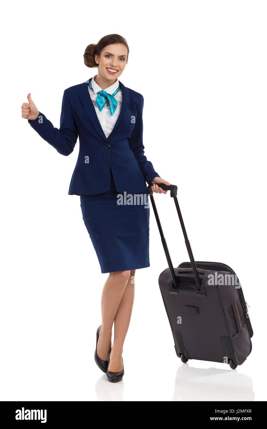 Mujer sonriente en traje azul y la falda de pie con trolley bolsa, mostrando el pulgar hacia arriba y mirando a Imagen De Stock
