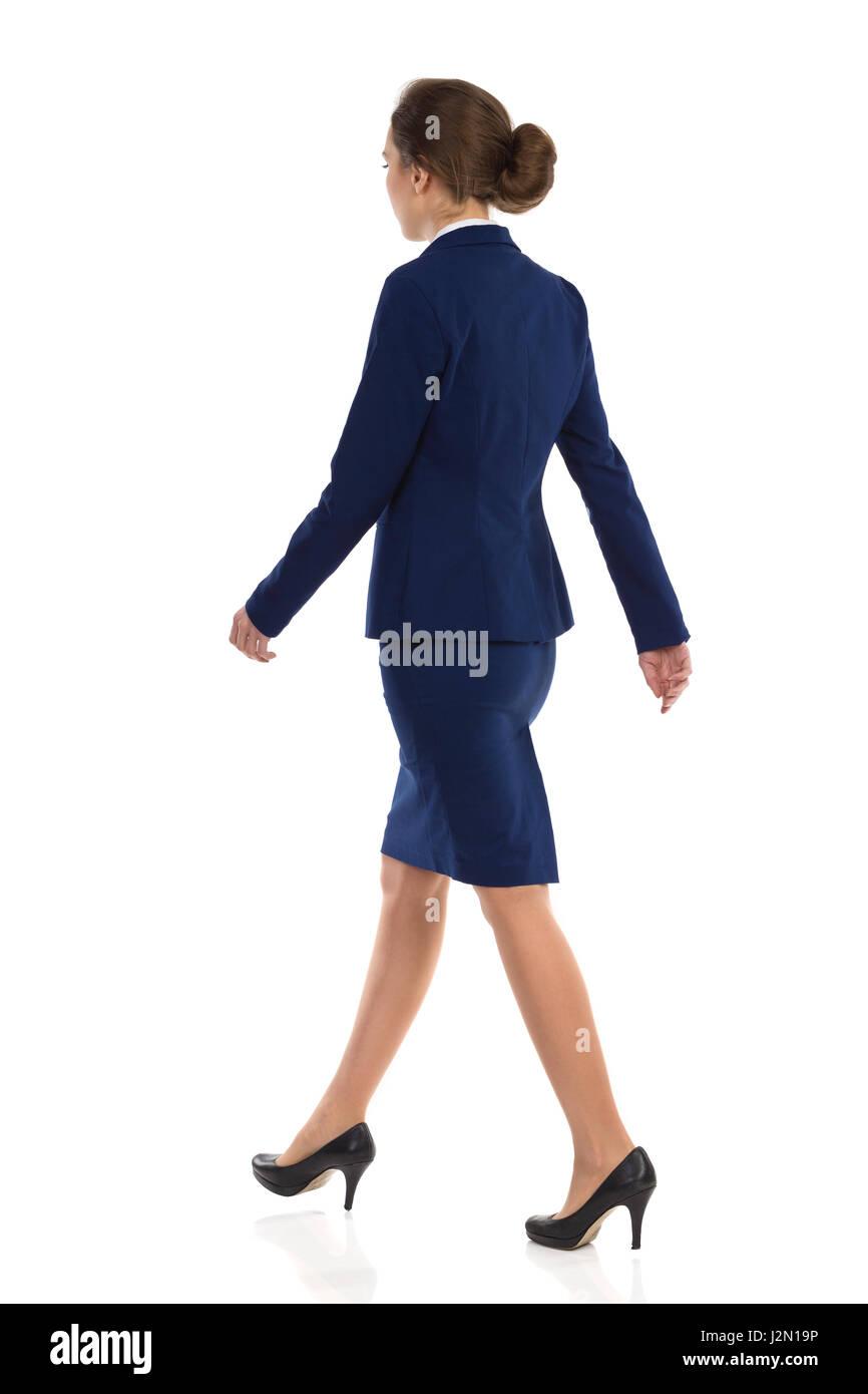 Mujer joven con traje azul, falda y zapatos de tacón negro caminando. Vista de la parte trasera. Longitud total Imagen De Stock
