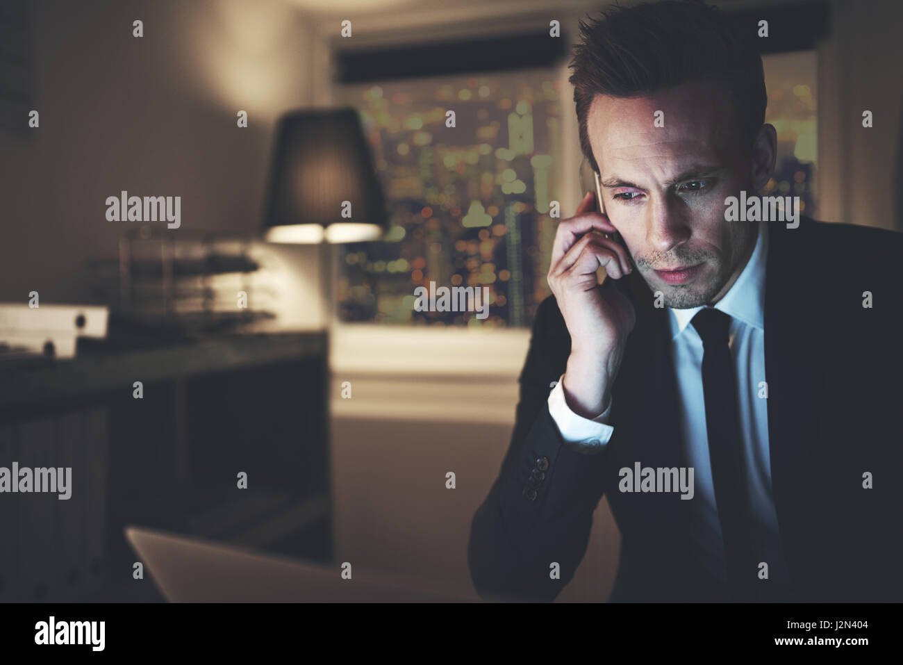 El contador trabajando tarde hablando smartphone mientras surf su portátil. Imagen De Stock