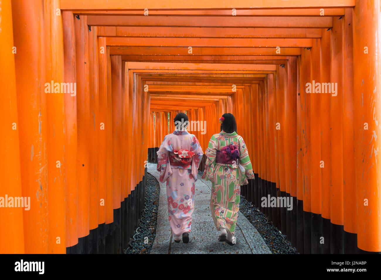 Dos geishas entre madera roja en Fushimi Inari Tori Gate santuario en Kyoto, Japón. Las mujeres vestidas con Imagen De Stock