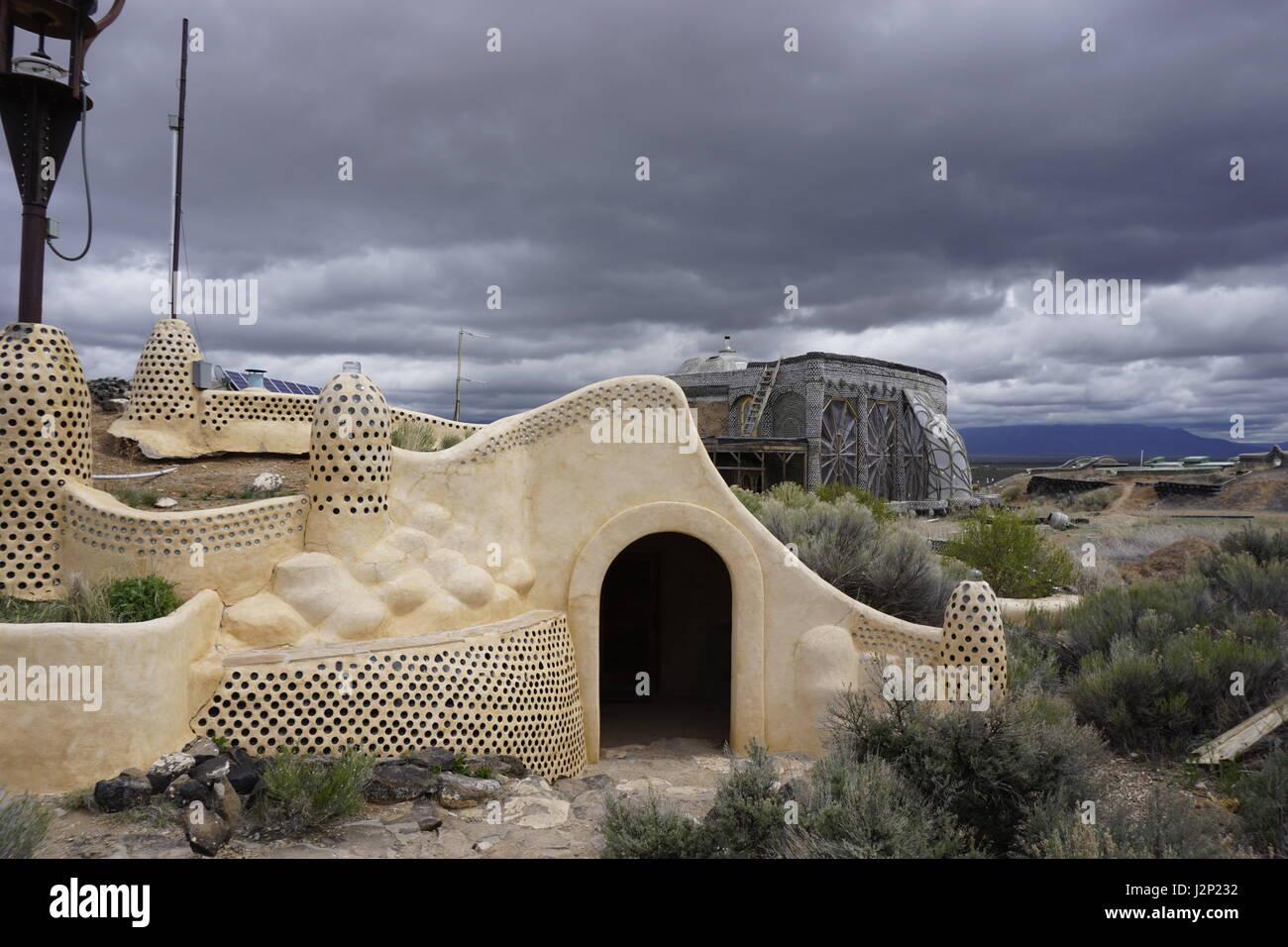 Nubes de tormenta rodar dos últimos off-grid, sostenible earthship Biotecture Earthship estructuras en el centro para visitantes cerca de Taos, Nuevo México, EE.UU.. Foto de stock