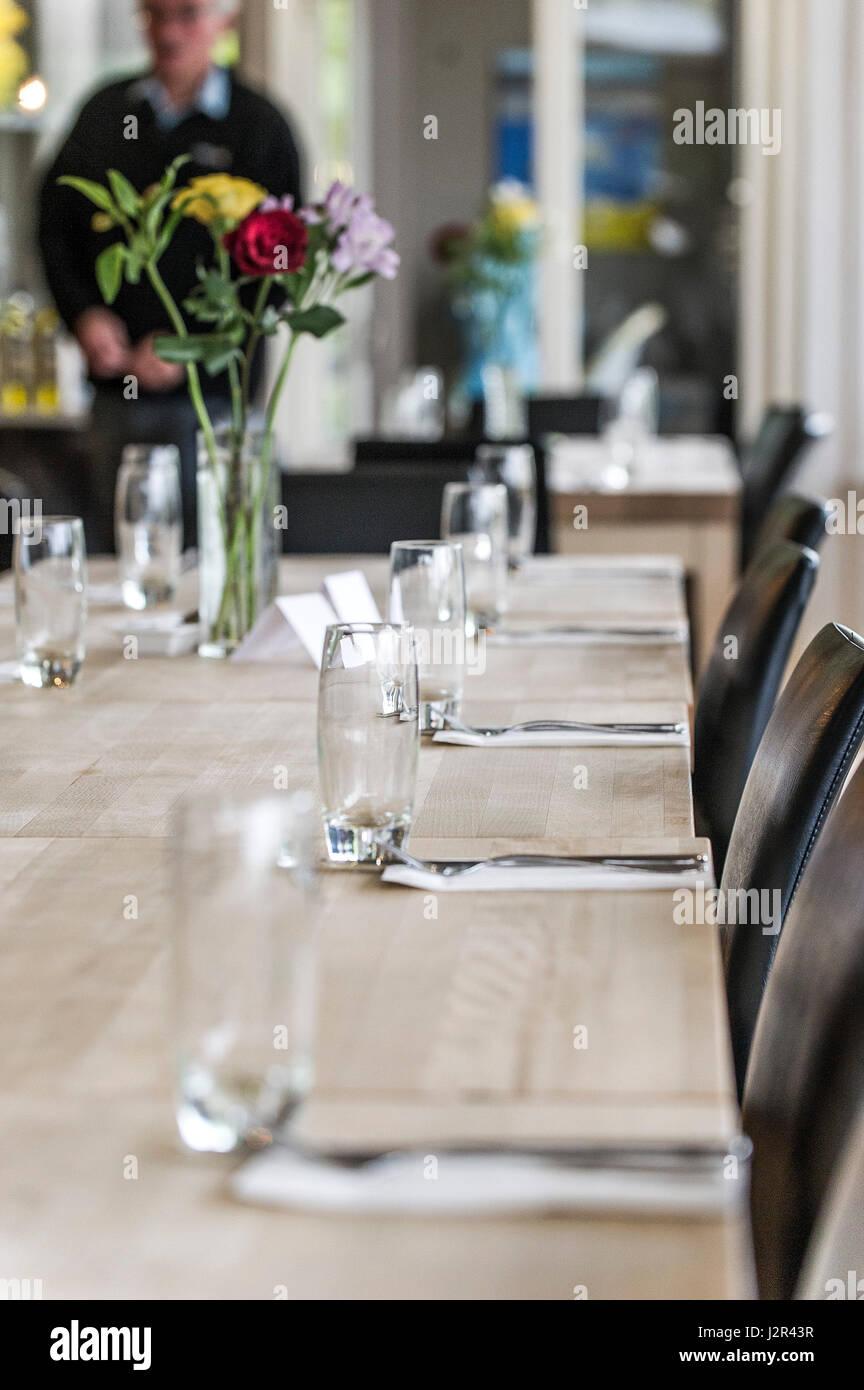 Gafas vacía sobre una mesa de comedor vasos cubiertos limpios sin usar el restaurante interior Imagen De Stock