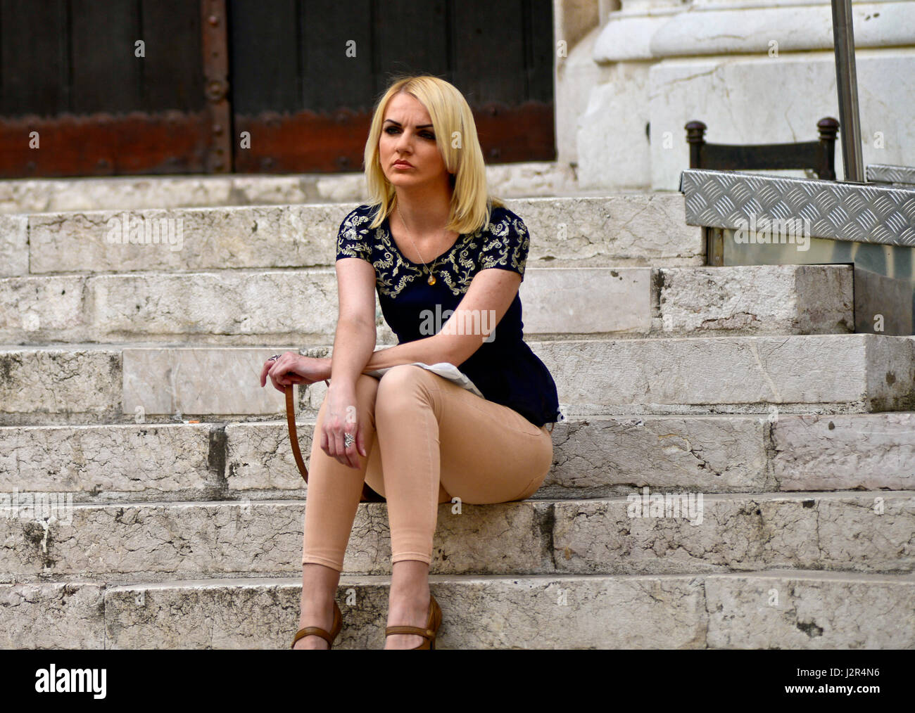 Una mujer rubia, esperando en las escaleras de una iglesia Imagen De Stock