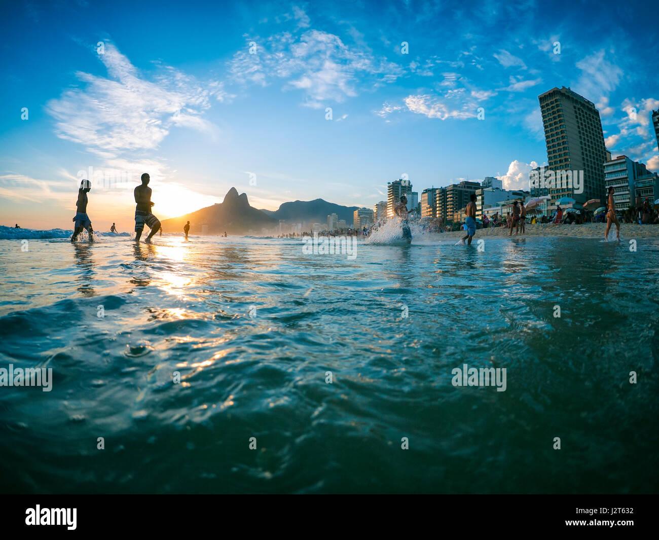 RIO DE JANEIRO.- El 2 de febrero de 2013: siluetas pasa por delante de la puesta de sol en la orilla de la playa Imagen De Stock