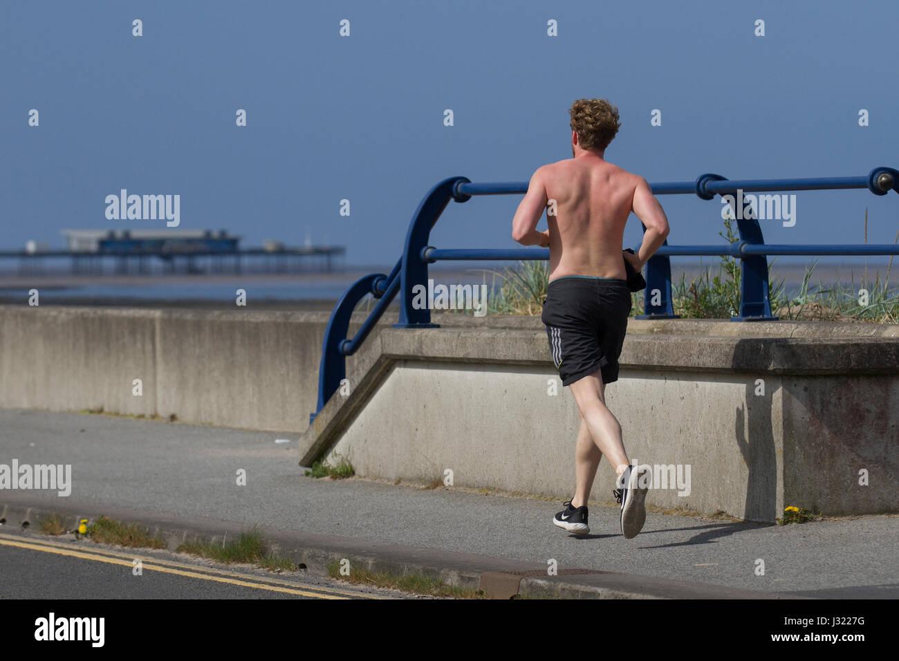 Vista trasera del hombre corriendo en Southport, Merseyside, Reino Unido. El clima del Reino Unido. El 2 de mayo, Imagen De Stock