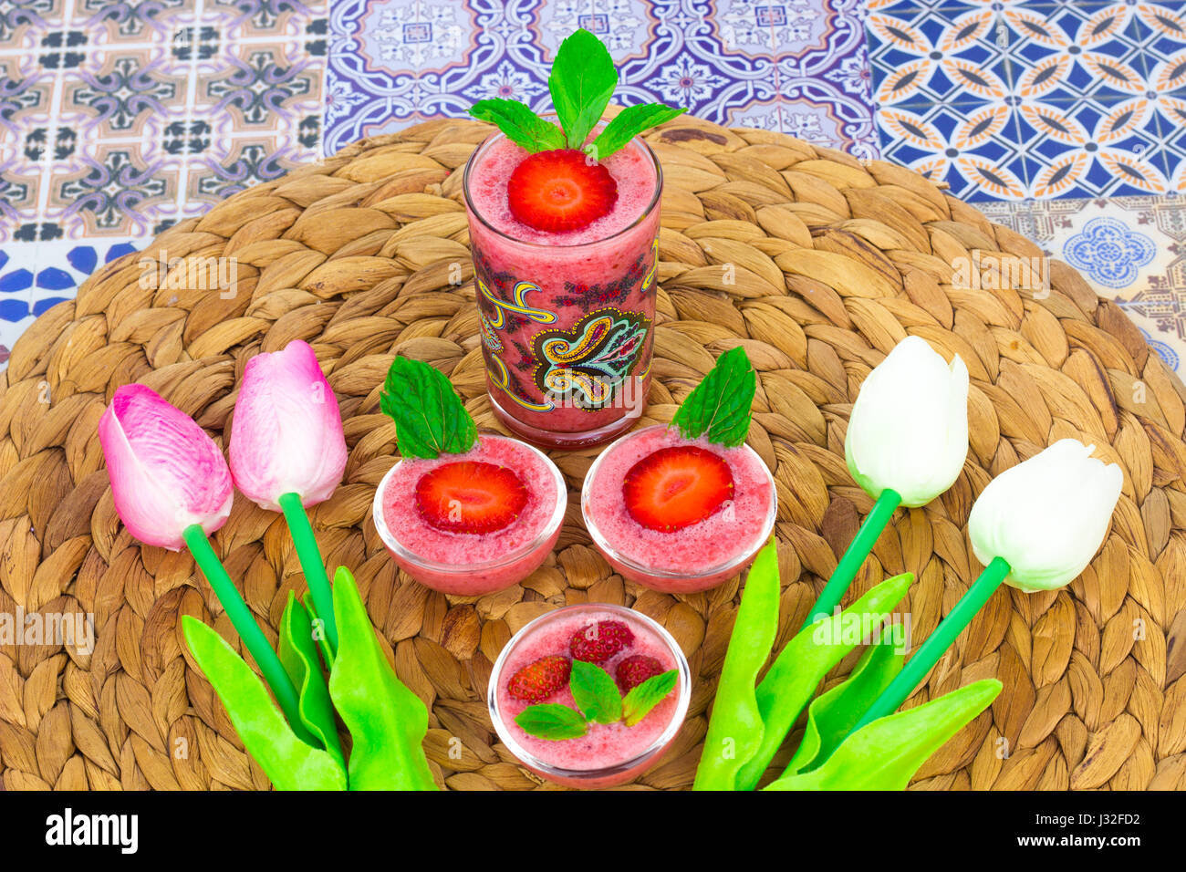 Una taza de jugo de fresas con hojas de menta sobre un fondo de colores orientales / taza de jugo de fresas sobre un fondo de colores orientales con flor Foto de stock