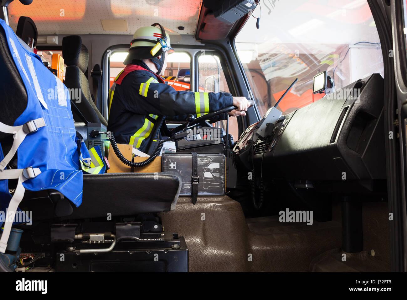 Unidades de bomberos alemanes en un camión de bomberos en acción y utiliza un walkie talkie Imagen De Stock