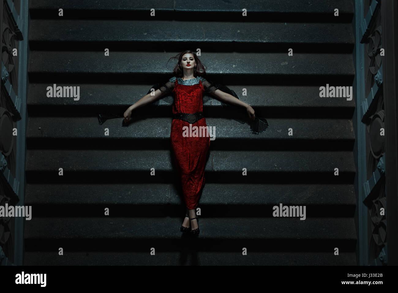 Chica gótica cayó sobre las escaleras en la noche. Es un extraño y sugestivo el horror y el miedo. Imagen De Stock