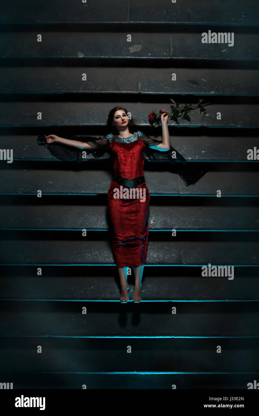 Chica con una rosa roja tumbado en las escaleras en la noche. Este gótico y ataca el miedo y el terror. Imagen De Stock
