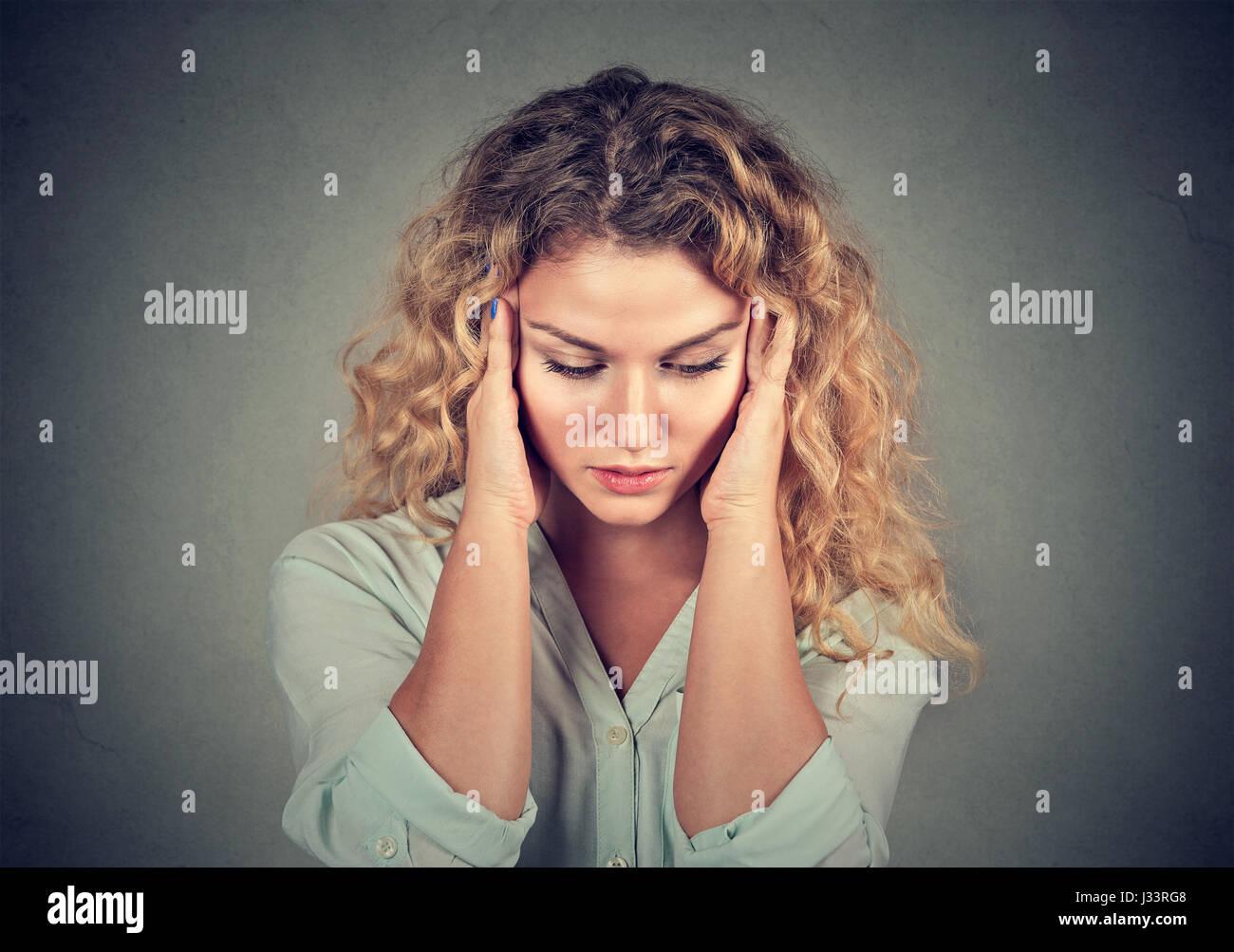 Closeup retrato triste hermosa mujer joven con expresión de cara destacó preocupados mirando hacia abajo Imagen De Stock