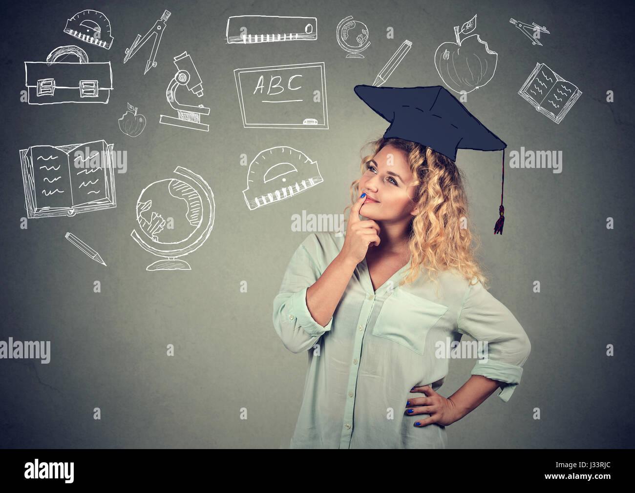 Hermosa joven mujer de negocios con graduación hat busca pensar la educación aislado sobre fondo de pared Imagen De Stock