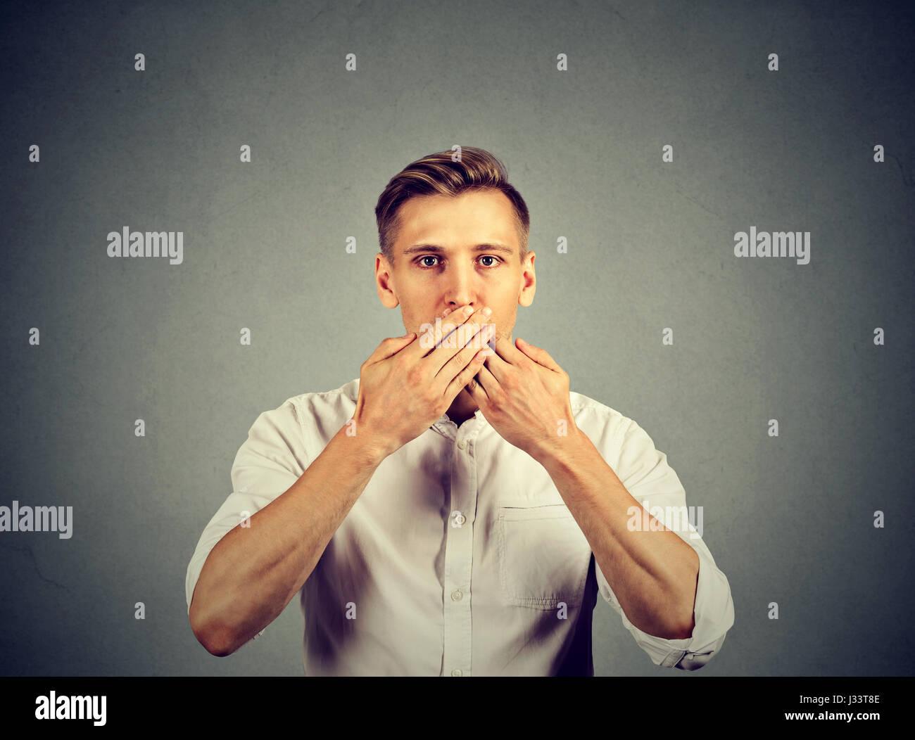 El hombre con la mano sobre su boca, mudo aislado sobre fondo de pared gris Imagen De Stock