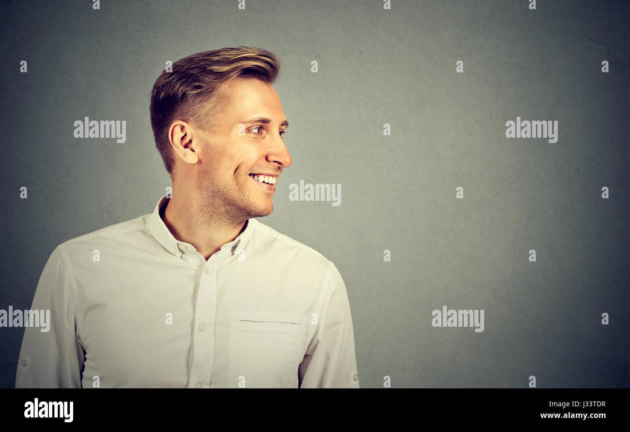 El perfil lateral joven mirando su cara sonriente Imagen De Stock