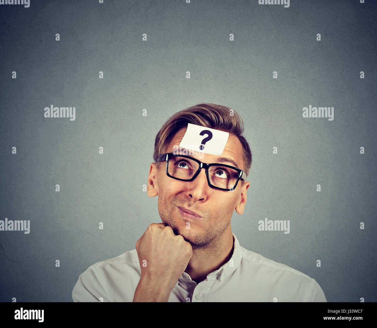 Hombre pensante con signo de interrogación sobre la pared gris antecedentes Foto de stock