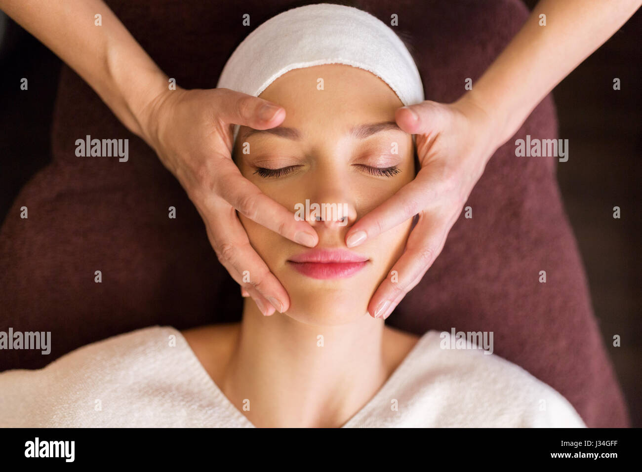 En el rostro y en la cabeza una mujer con un masaje en el spa Imagen De Stock