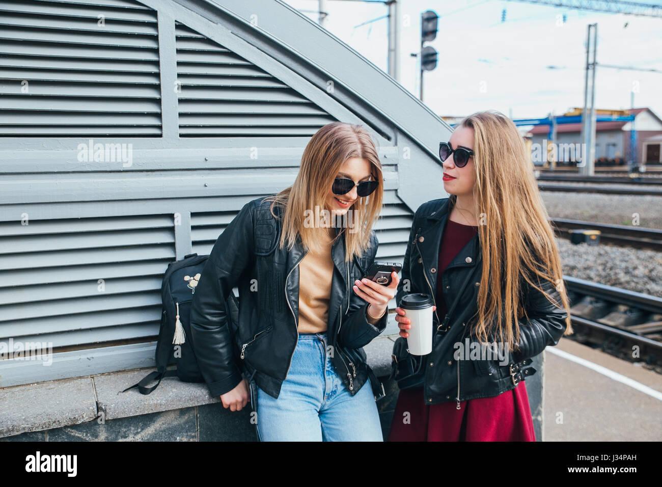 Dos mujeres hablando en la ciudad.Outdoor Lifestyle retrato de dos mejores amigos hipster niñas vestían eleganteFoto de stock