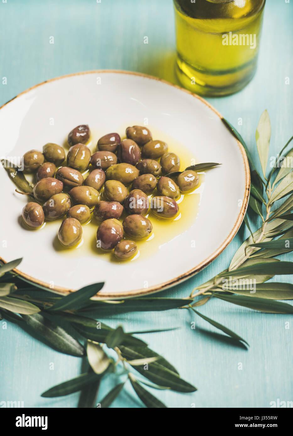 Encurtido de aceitunas verdes, rama de olivo, aceite virgen, el enfoque selectivo Imagen De Stock
