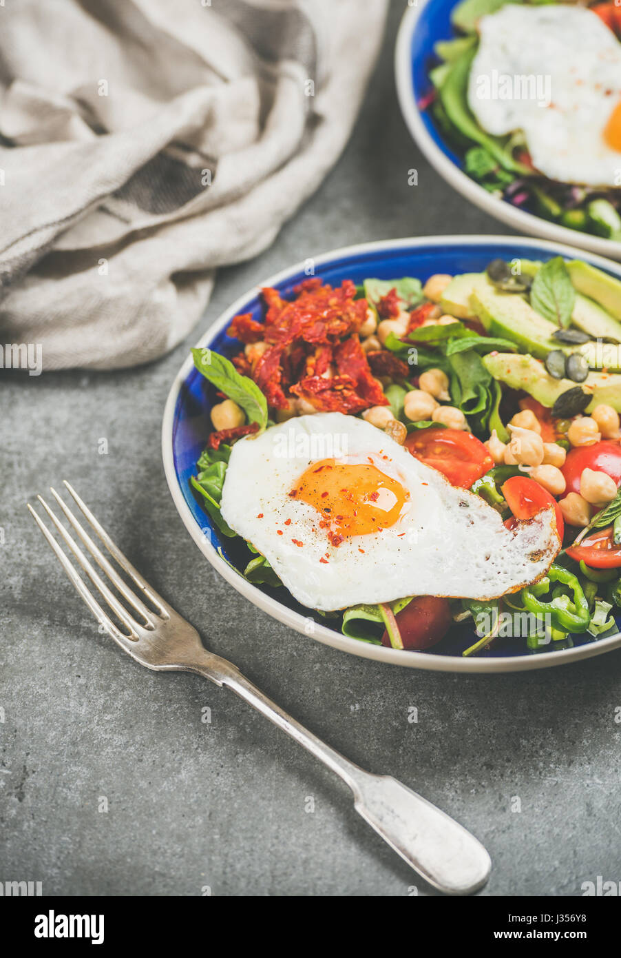 Concepto vegetariano desayuno con huevo frito, garbanzos, hortalizas, semillas Imagen De Stock