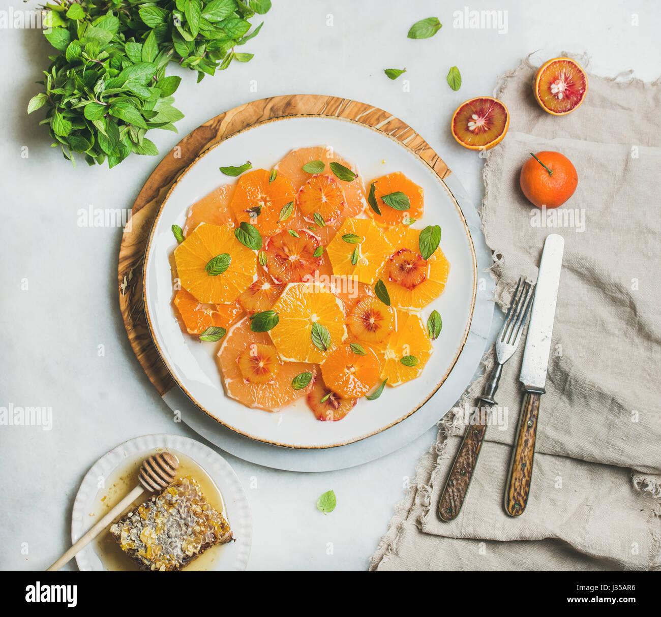 Fresca ensalada de frutas cítricas mezcladas con menta y miel Imagen De Stock