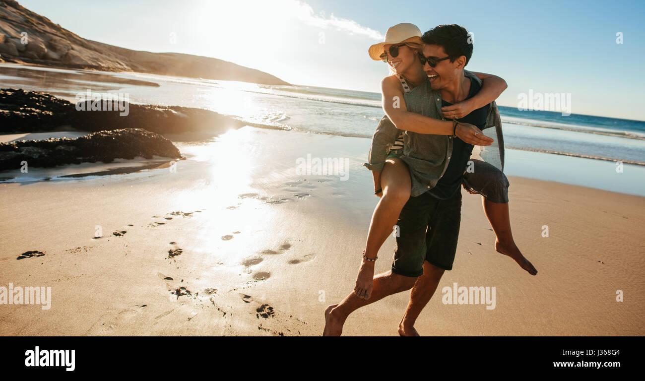 Hombre haciendo piggyback paseo a la novia en la playa. Feliz pareja joven divirtiéndose en la orilla del mar, Imagen De Stock