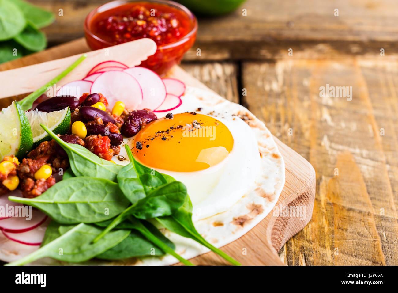 Huevo frito tacos con chili con carne en junta de corte rústico, comida tradicional mexicana Imagen De Stock