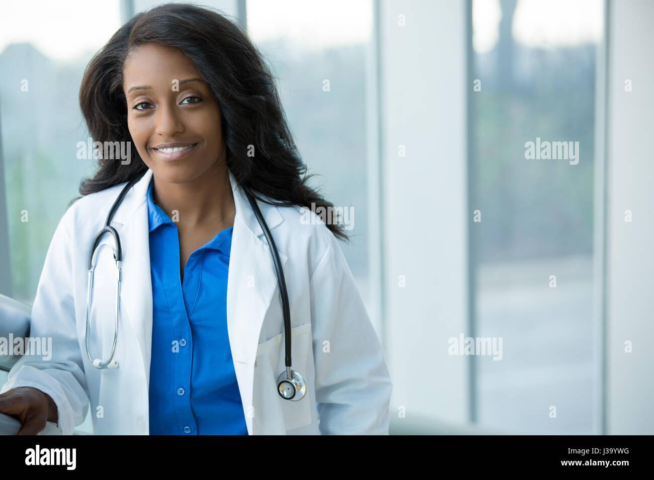 Closeup retrato de agradable, sonriente, seguro de salud femenina con bata de laboratorio profesional, el estetoscopio, brazos cruzados. Hospital clínico aislado atrás Foto de stock