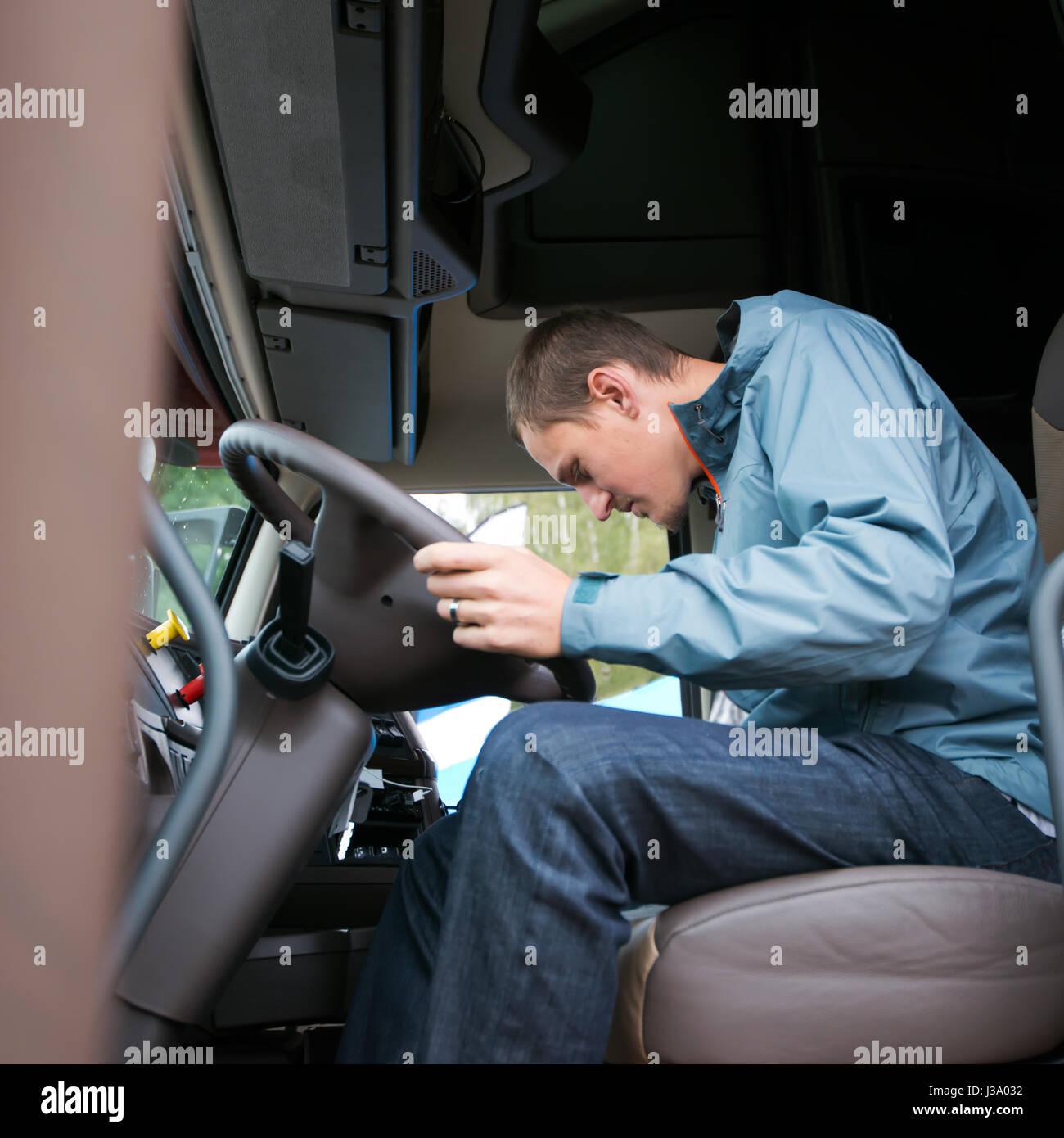 Joven conductor de camión se asienta en una cómoda cabina del camión moderno y verificar la idoneidad Imagen De Stock