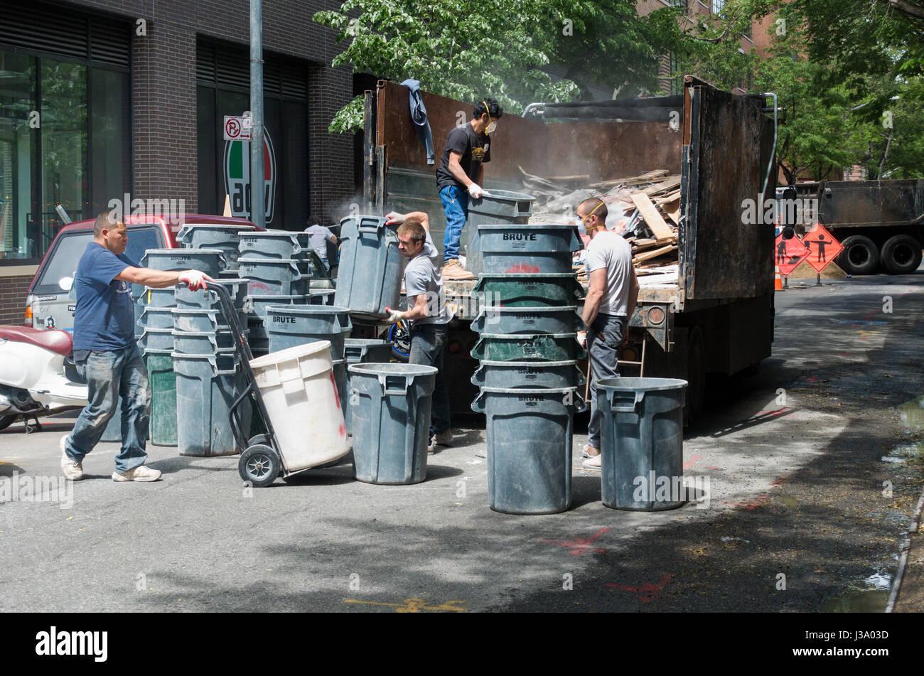 Cuatro hombres la remoción de escombros de construcción en grandes cubos de plástico n la ciudad Imagen De Stock