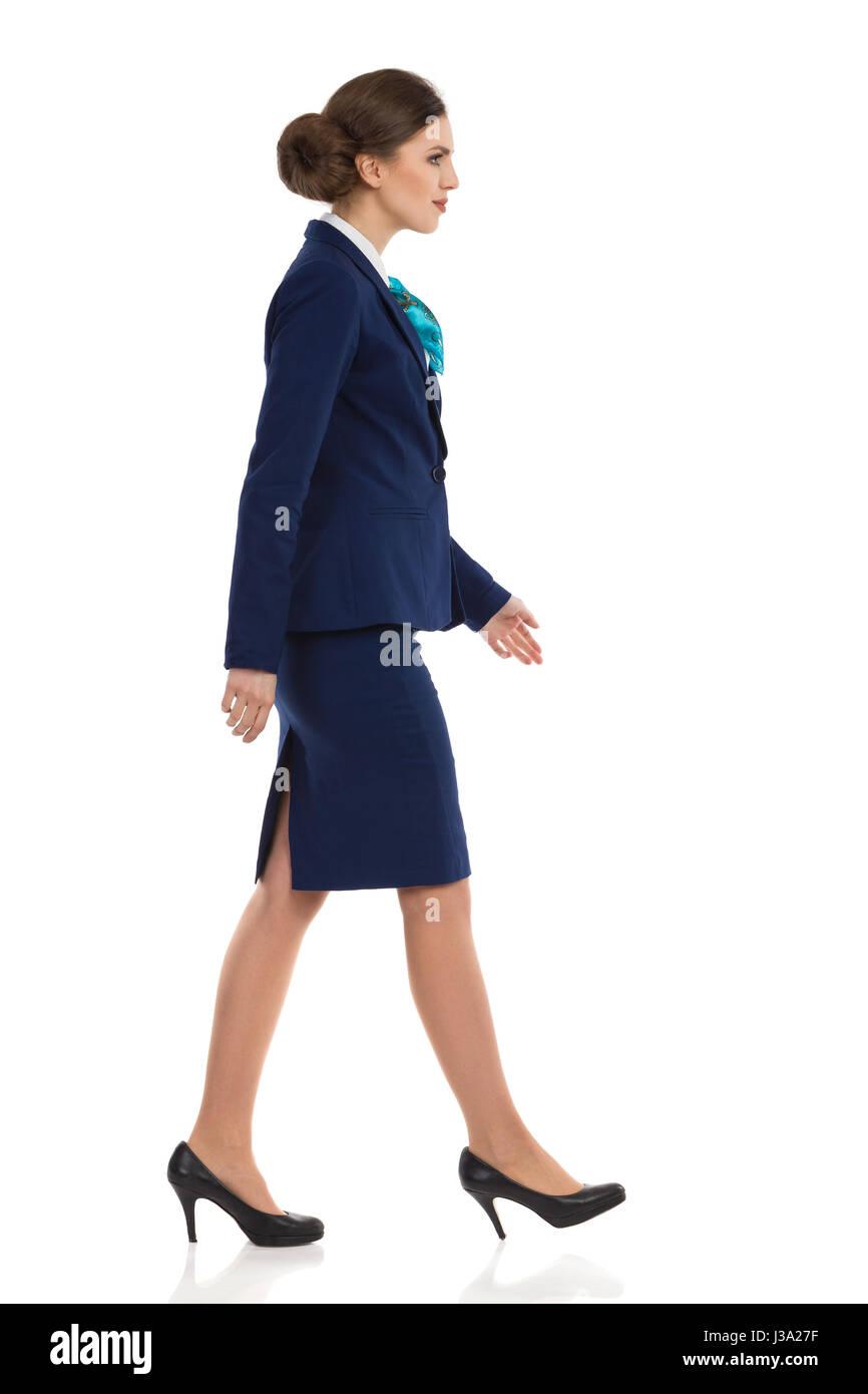 Mujer elegante en azul traje, falda y tacones al caminar. Vista lateral. Longitud total studio shot aislado en blanco. Imagen De Stock