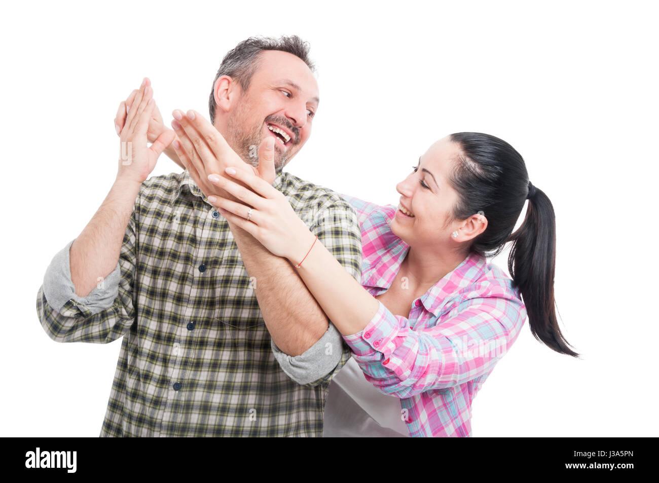 Encantadoras mujeres sorprendente su guapo amante y sonriendo juntos sobre fondo blanco. Imagen De Stock