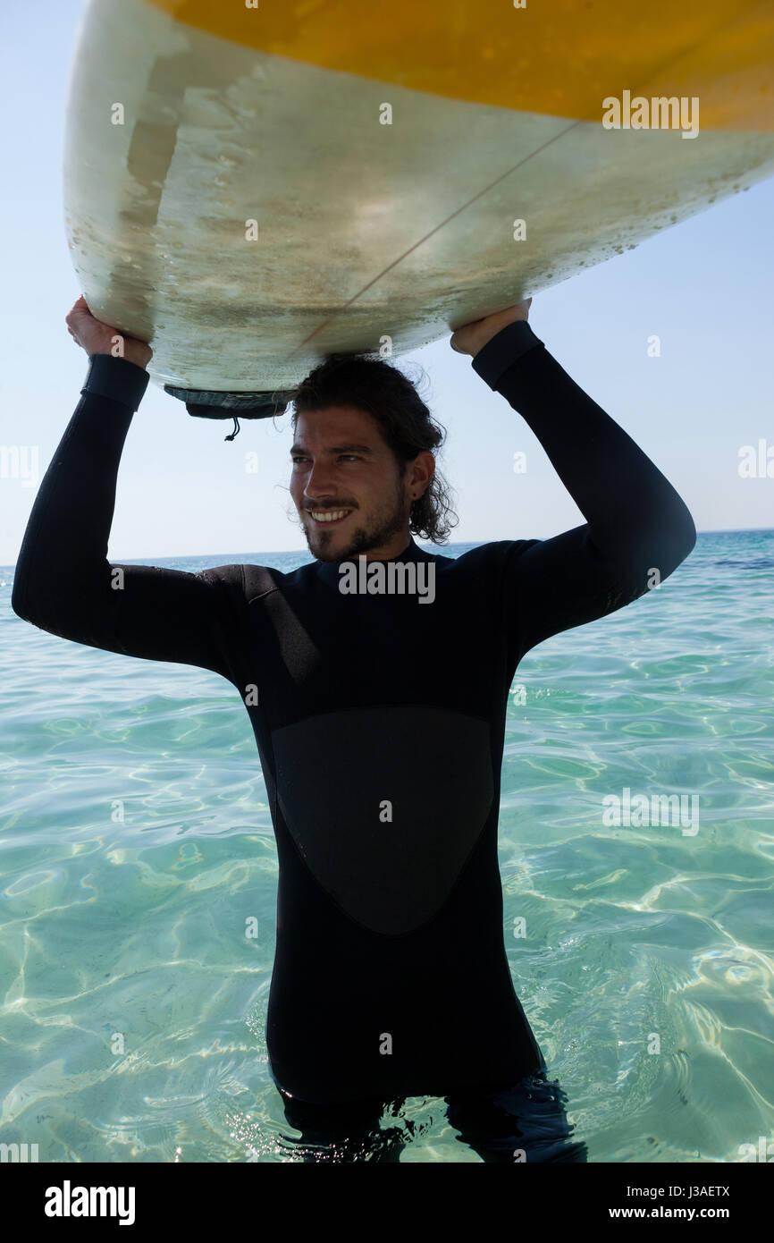 Surfer sonriente en llevar traje de neopreno, tablas de surf sobre la cabeza en playa costa Foto de stock