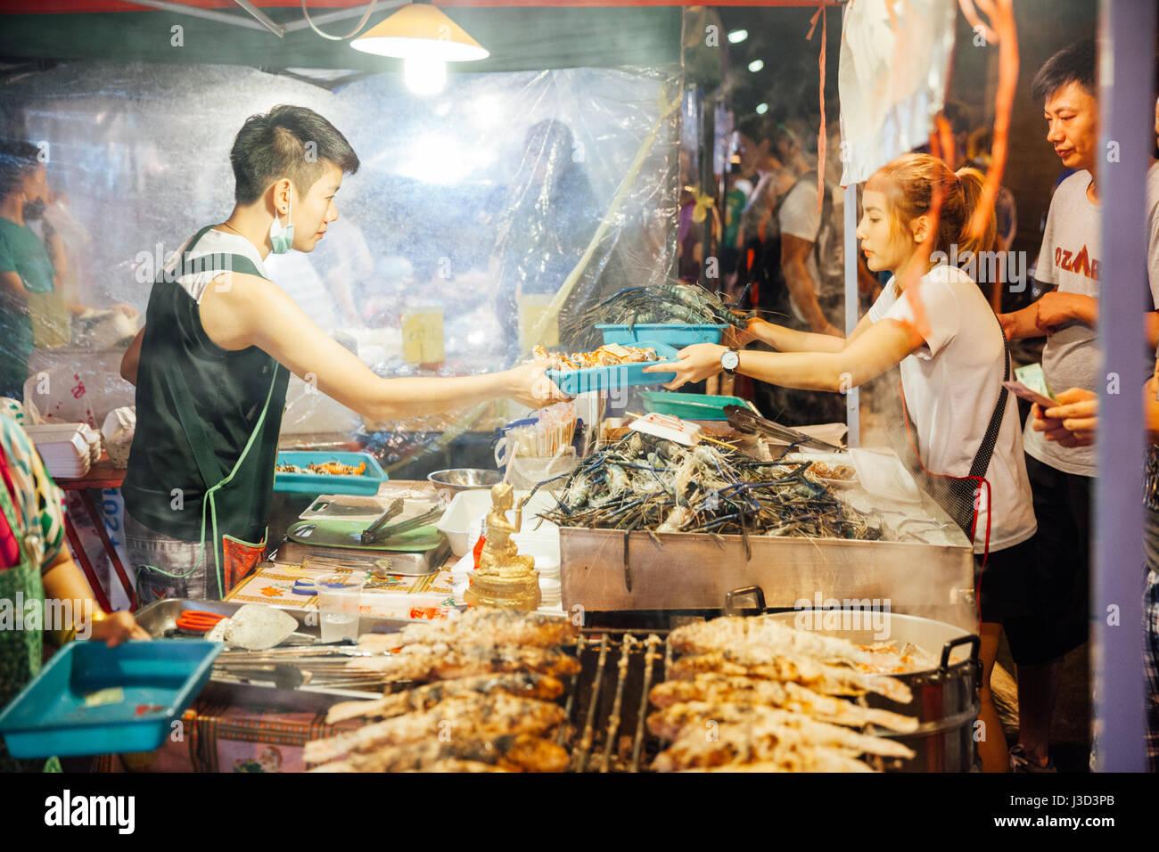 CHIANG MAI, Tailandia - 27 de agosto: vendedor de comida cocineros y vende pescado y marisco en el mercado del sábado Imagen De Stock