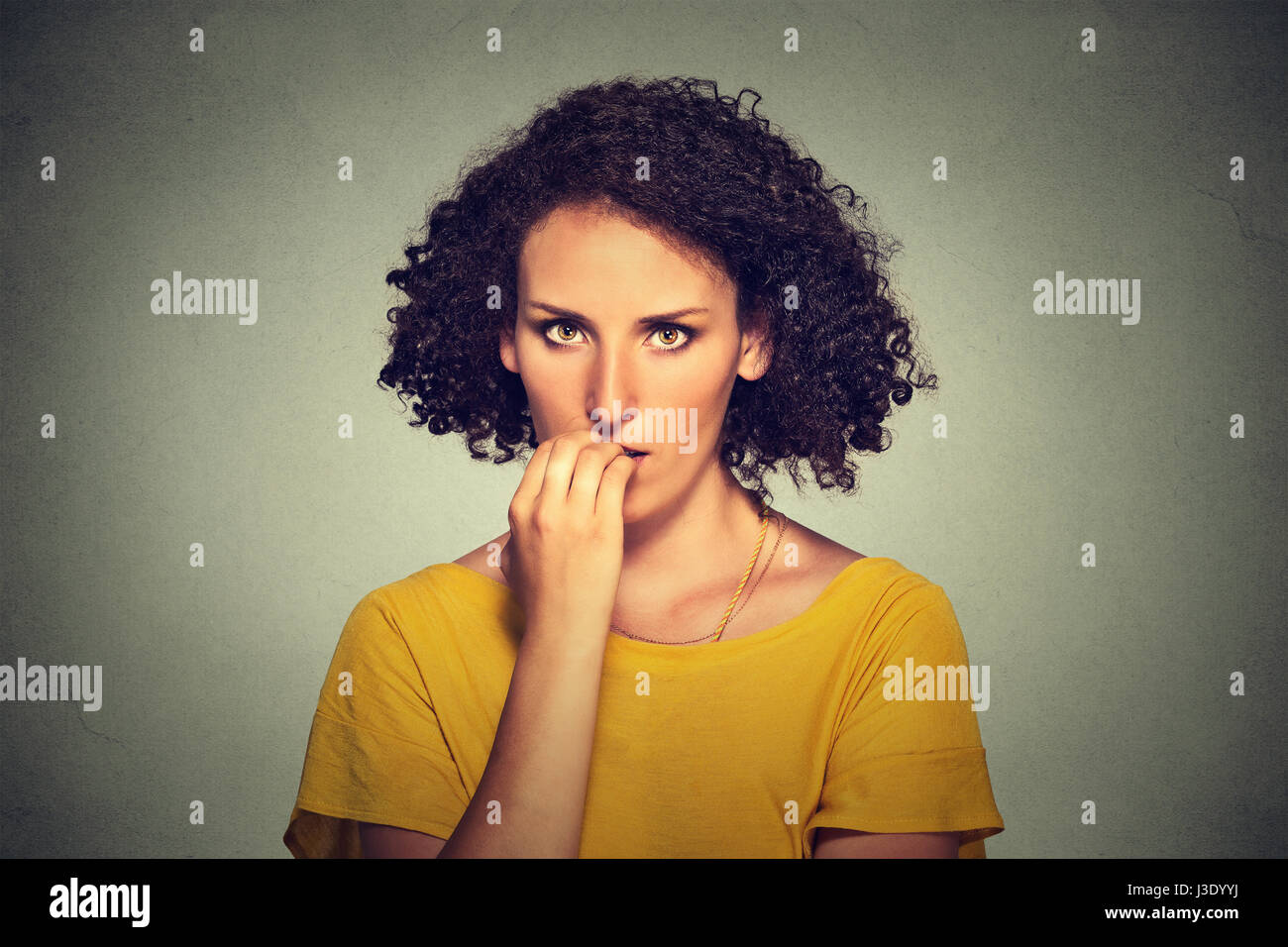 Las preocupaciones. Closeup retrato Mujer mirando nervioso mordiendo las uñas anhelando algo ansiosos aislado Imagen De Stock