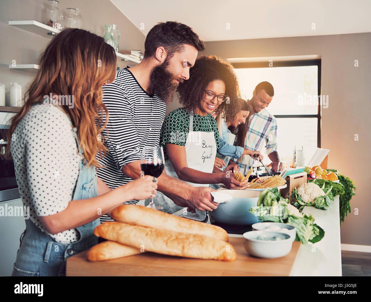 Gran grupo de seis amigos preparando la comida para una clase de ...