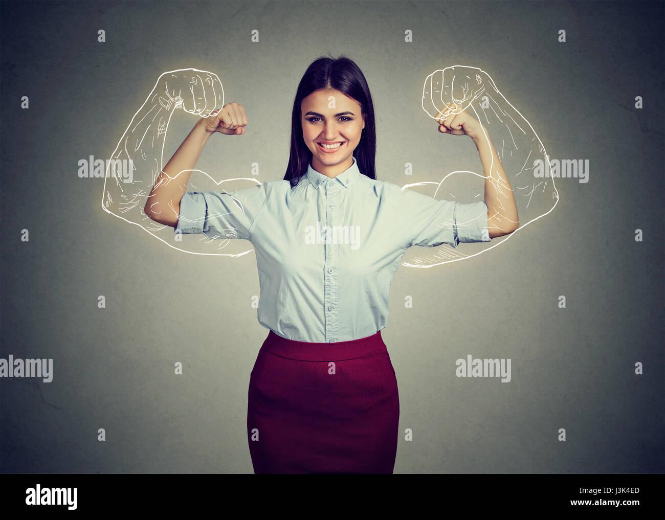 Potente seguros mujer flexionando sus músculos aislados en la pared gris de fondo. Expresiones de rostro humano, Imagen De Stock