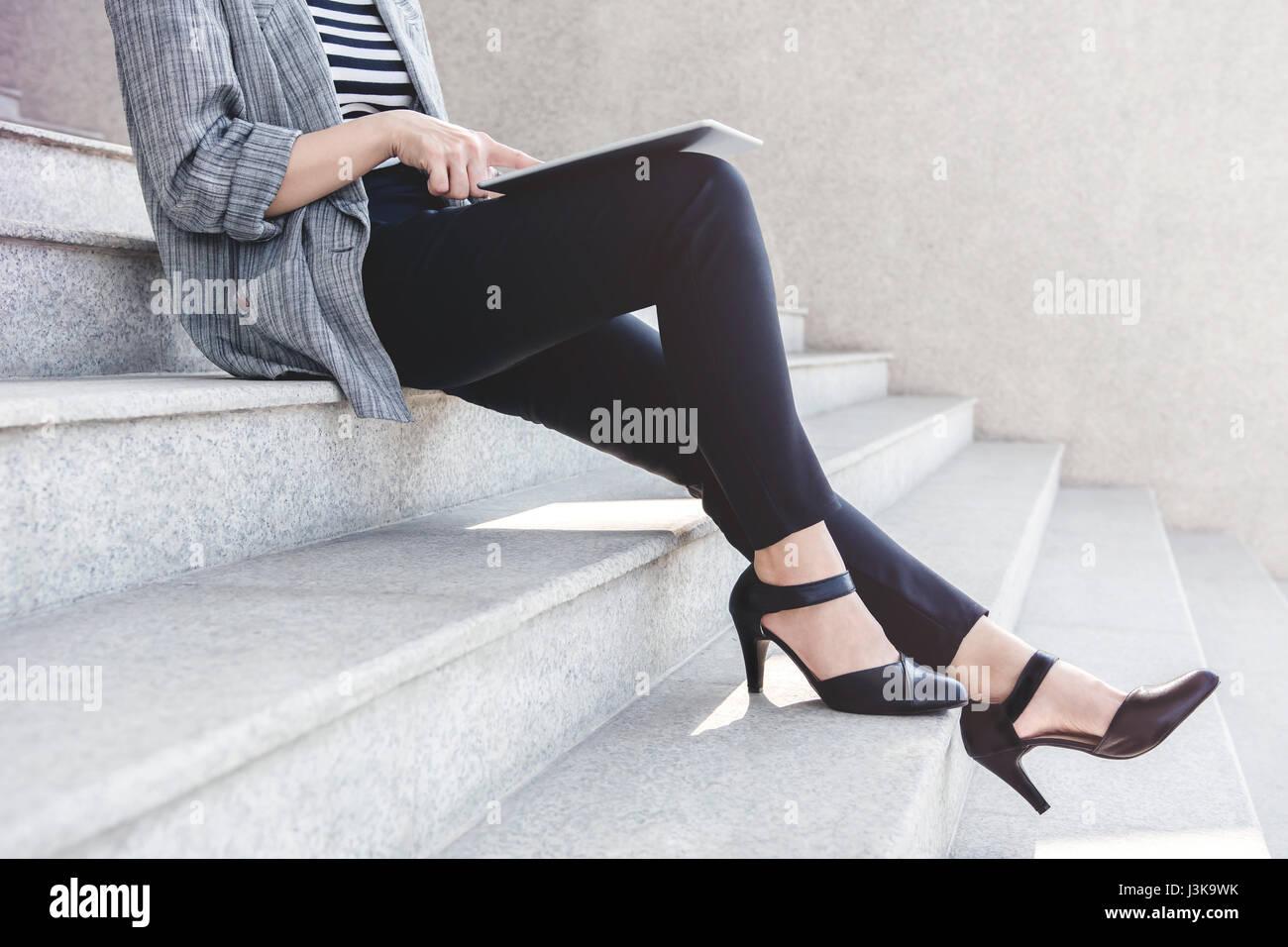 Negocio trabajar mujer sentada y utilizando tablet digital en escalera exterior, vista lateral, Sociales comunicar Imagen De Stock